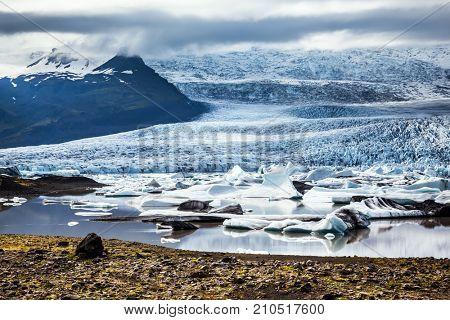 Sunset lights glacier Vatnajokull - the biggest glacier in Iceland. Glacier provides water Ice Lagoon Jokulsarlon. The concept of northern extreme tourism