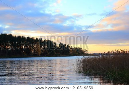 Autumn nature. Sunset on the lake. Evening landscape. Clouds over the lake. The horizon at sunset. Skyline at sunset. The waves on the river. Shore of the lake. The lake in Russia