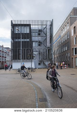 groningen, netherlands, 8 oktober 2017: young people on bicycle pass building of architecture academy in dutch city of groningen