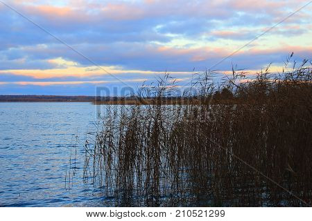 Autumn nature. Sunset on the lake. Evening landscape. Clouds over the lake. The waves on the river. Shore of the lake. The lake in Russia
