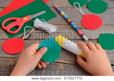 Child makes Christmas balls out of cardboard. Child carves and glues Christmas balls from cardboard. Step. Stationery on the table. Paper Christmas ornaments kids craft