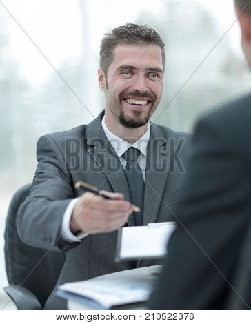closeup.smiling businessman signing a lucrative contract.the business concept.