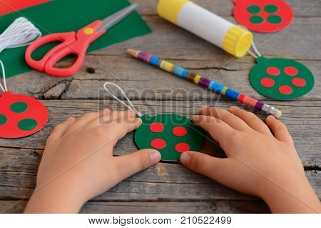 Child made bright Christmas balls from cardboard paper. Child shows Christmas ball. Step. Scissors, pencil, glue stick on an old wooden table. Homemade easy Christmas tree decorations for children