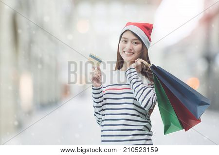 Young beautiful Asian woman shopping with credit card in Christmas holiday. Holding shopping bag and wearing Christmas hat with smiling face on blurred shopping center background.