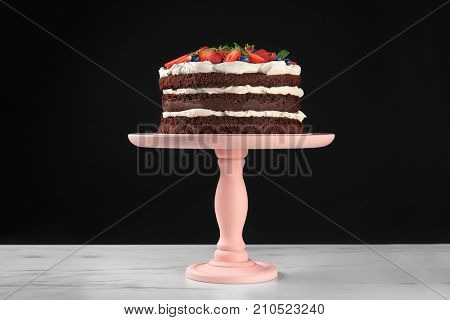 Dessert stand with delicious chocolate cake on table against black background