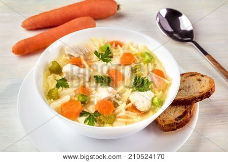 A photo of a plate of chicken, vegetables, and noodles soup, shot on a light texture with slices of bread, carrots, and a spoon, selective focus