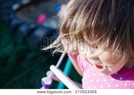 Little girl swing outdoor portrait with come uncurled hairs child playing activity