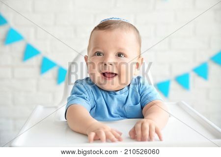 Cute baby in kippah sitting on high chair against brick wall