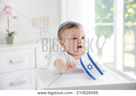 Cute baby in kippah with flag of Israel sitting on high chair at home