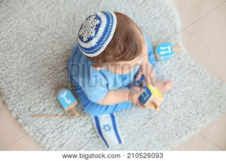 Cute baby in kippah playing with dreidels while sitting on floor