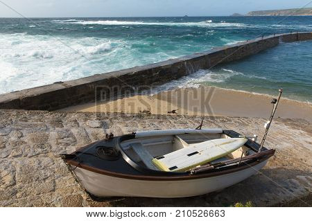 Sennon Cove Cornwall rowing boat and harbour wall with blue sea and white waves