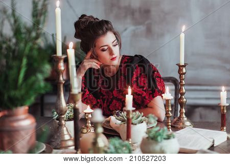 Cheerful young woman in old fashion dress reading book in restaurant decorated for Christmas. Waiting for date. Horizontal shot.