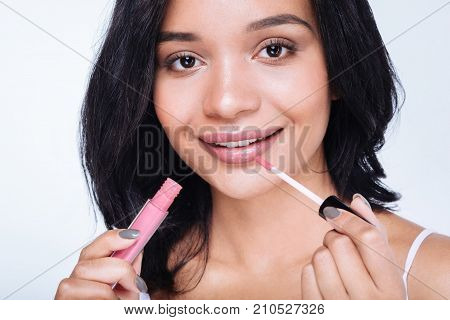 Charming beauty. The close up of a pretty young woman with a swarthy complexion applying pink lip gloss to her lips and smiling at the camera while standing against white background