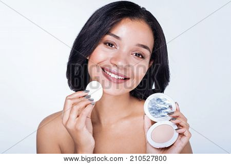 New cosmetics. Beautiful dark-haired young woman with a swarthy complexion showing her new powder and a puff while standing isolated on a white background