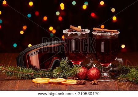 Mulled wine, fir branches, ski glasses and  christmas decoration on a wooden table on a dark background with light of garland. Winter vacation.