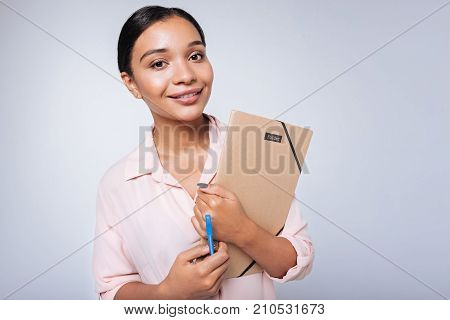 Ready to work. Charming young woman with a swarthy complexion holding a document folder and a blue marker while standing against a blue background