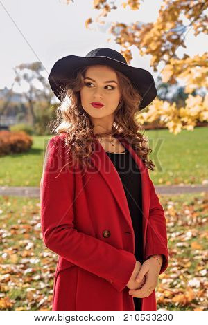 portrait of an aristocratic girl walking in an autumn park in a red coat and a black hat