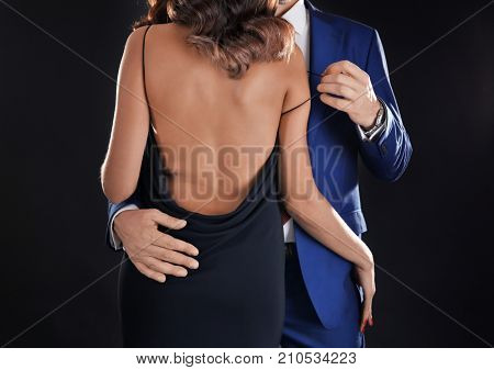 Man in formal suit undressing woman on black background poster