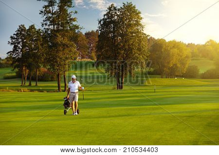 Handsome man golfer walking on fairway at golf course in the summer evening