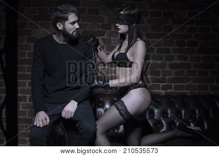 Young dominatrix in blindfold offering handcuffs to man in dark