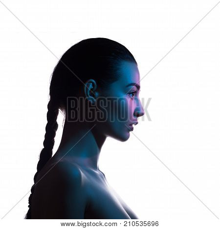 Art fashion studio portrait of nude elegant woman on white background. Profile of attractive mixed race Asian Caucasian female model with braid. Perfect slim body. Beauty and health. Colored profashional lights
