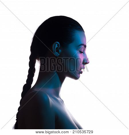 Art fashion studio portrait of nude elegant woman with closed eyes on white background. Profile of attractive mixed race Asian Caucasian female model with braid. Perfect slim body. Beauty and health. Colored profashional lights
