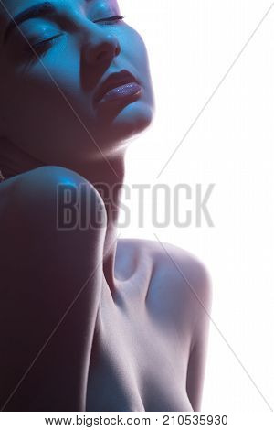 Close-up art fashion studio portrait of nude sensual woman with closed eyes on white background. Profile of attractive mixed race Asian Caucasian female model. Perfect slim body. Beauty and health. Colored profashional lights