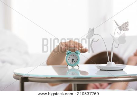 Woman turning off alarm clock in morning