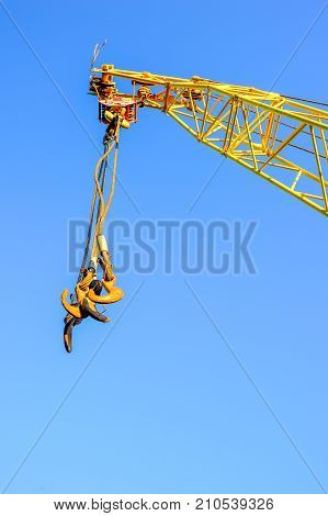 Four empty yellow crane hook hanging down isolated on white background.