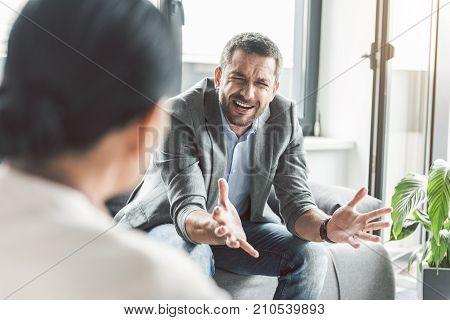 Upset man is sitting afore psychologist and telling his problems. He locating on sofa. Portrait. Copy space on left side