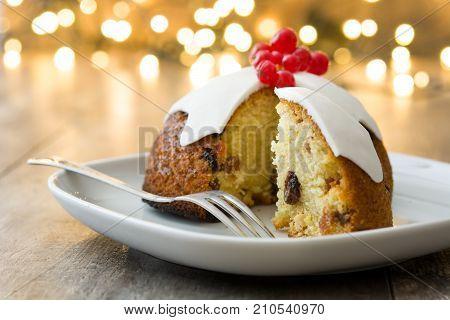 Christmas pudding and christmas light on wooden table
