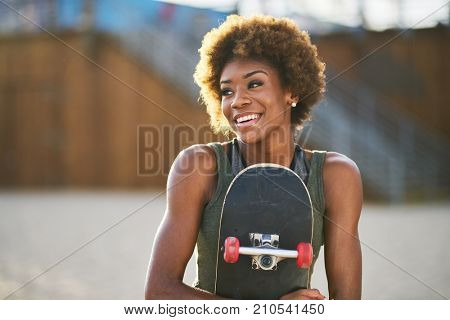 portrait of happy african american woman holding skateboard with natural hair