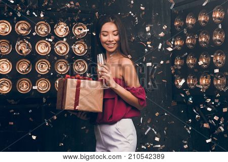 Pretty young funny girl smiling and having fun, holding holiday presents, drinking champagne and dancing. Christmas party. Happy 2018 To You!