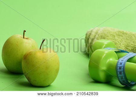 Dumbbells In Bright Green Color, Measure Tape, Towel And Fruit