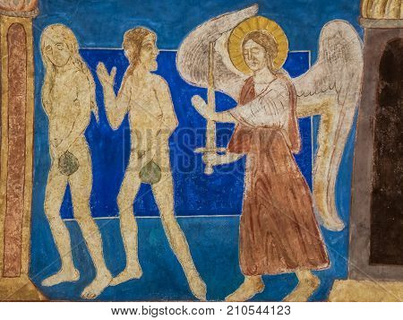 Adam and Eve are expelled from paradise by an angel holding a sword. Medieval mural in Bjaresjo church Sweden November 6 2009