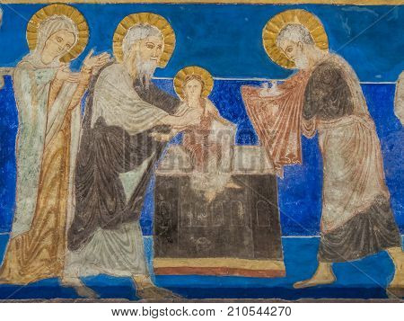 The presentation in the temple Simeon holds baby Jesus and Joseph come with two sacrificial doves in a cloth a romanesque wall-painting in Bjaresjo church Sweden November 6 2009