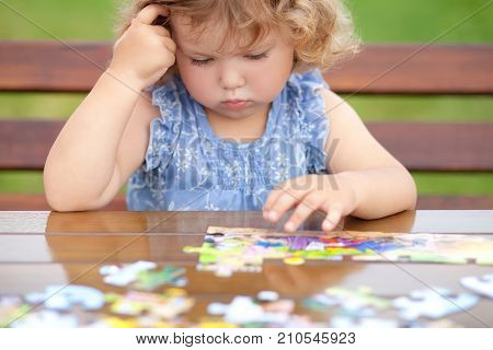 Blonde unhappy toddler girl solving puzzle on a table hard difficult task. Early education and developement. Little genius concept. Emotional. poster
