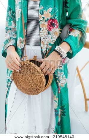 Stylish woman's outfit. Green stylish top. Straw bag. White dress. Trendy casual outfit. Street fashion. Details of everyday look.