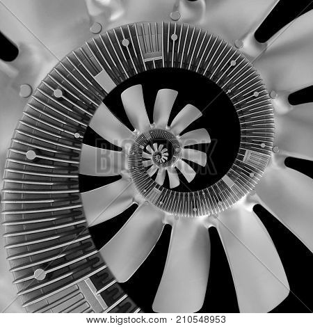 Isolated on black abstract spiral fractal made of truck diesel engine fan silver air screw. Spiral background pattern engine fan. Truck engine fan abstract spiral effect Surreal coil effect truck part