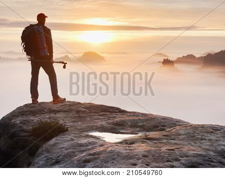 Tired Hiker With Sporty Backpack On Rocky Peak  And Watching Into Deep Misty Valley Bellow.
