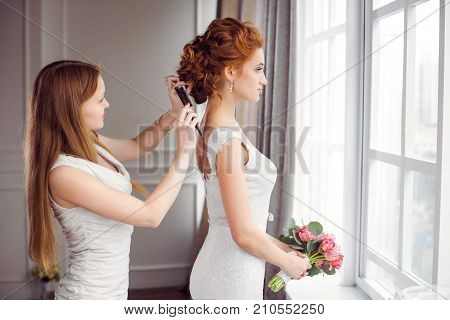 Master stylist makes the bride wedding hairstyle using hairbrush indoors at home near window. Beautiful bride perfect style. Wedding hairstyle make-up luxury wedding dress.