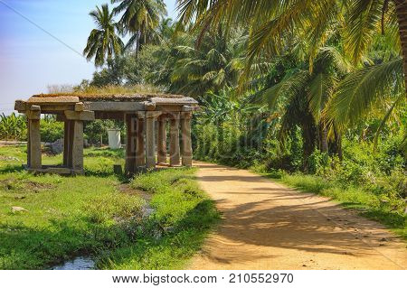 Ancient ruins on the way to the Lakshmi Narasimha Temple and Badaviling Temple in Hampi, Karnataka, India. Sandy road in the shade of palms. UNESCO World Heritage Site