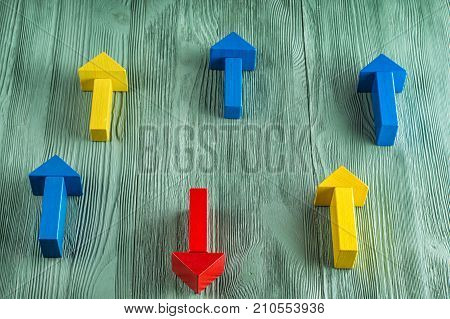 Wooden arrows on wooden background one arrow in opposite direction from others. The concept of independent thinking individuality uniqueness. Business concept another way.