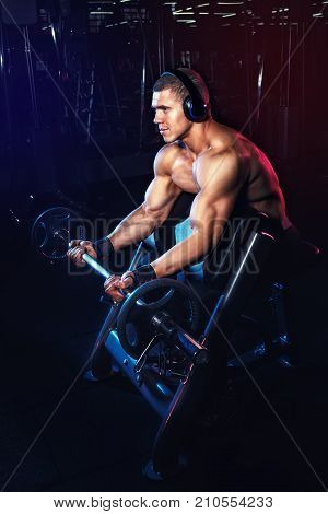 Bodybuilding concept. Muscular man doing exercises for biceps with barbell on Scott's bench in gym and listening music on headphones. Bodybuilder lifting weights. Power fitness man training muscles