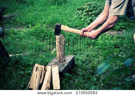 hands chopping wood firewood sledgehammer in summer