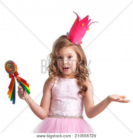 Beautiful little candy princess girl in crown holding big lollipop and posing with hands up in air saying, why, i dont know, so what