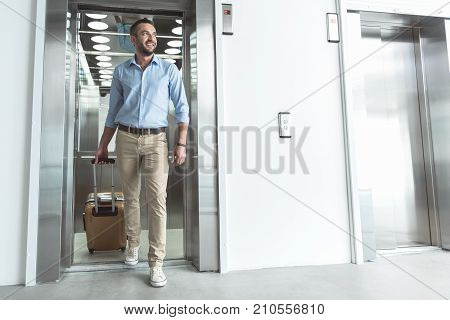 I like traveling. Full length portrait of delightful stylish businessman with stubble is exiting from modern lift while carrying his luggage. He is looking aside with smile. Copy space in the right side