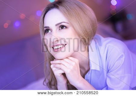 My dream. Attractive dark-eyed thoughtful woman smiling and feeling happy while dreaming of something