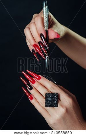 Holiday halloween or new year nail art design ideas. Beauty Fashion Hands Trendy Stylish Colorful manicure. Black Red fingers with rhinestones nailpolish isolated on black. Glamour and scary concept