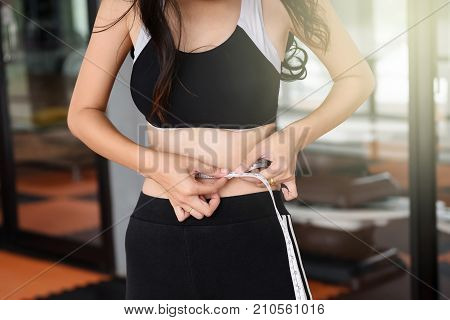 Asian skinny slim trainer girl 20-30 years old measuring her thin waist of 24 inch by tape measure at fitness gym club. Sport and Healthy lifestyle concept